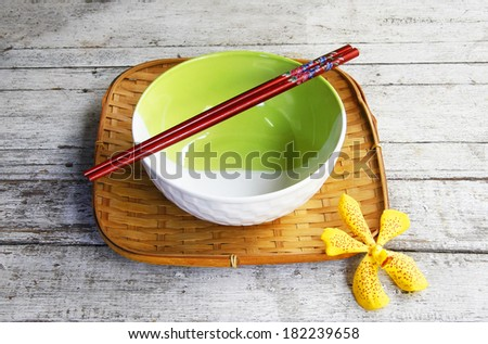ceramic bowl and chopsticks in bamboo tray on wooden table.  - stock photo