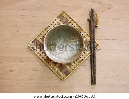 ceramic bowl (dish) and chopsticks on bamboo mat.Flat lay - stock photo