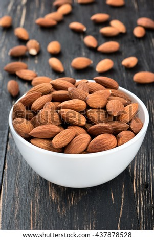 Ceramic bowl filled with scattered almond nuts on a dark table, closeup