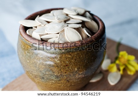 Ceramic bowl full of pumpkin seeds on kitchen table background - stock photo