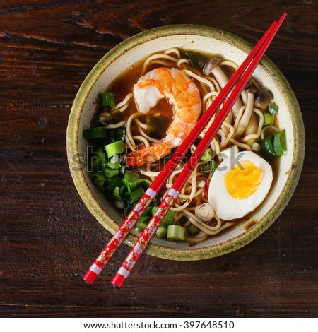 Ceramic bowl of asian ramen soup with shrimp, noodles, spring onion, sliced egg and mushrooms, served with red chopsticks over dark wooden surface. Flat lay. Square image - stock photo