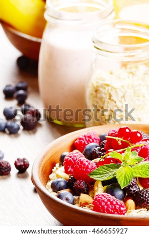 Ceramic bowl of oatmeal oats with berries nuts and yogurt