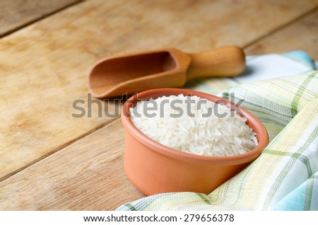Ceramic bowl of organic rice grains on the kitchen table - stock photo