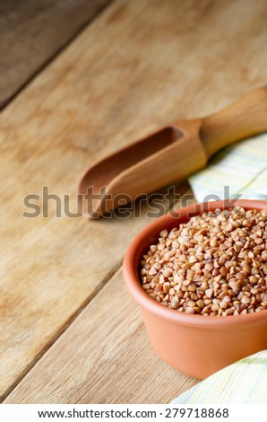 Ceramic bowl of roasted organic Buckwheat kernels on kitchen table - stock photo