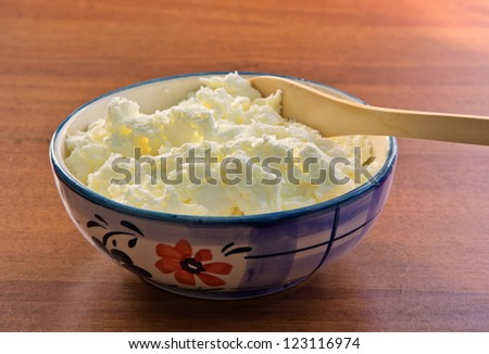 ceramic bowl with cottage cheese and a wooden spoon on the table