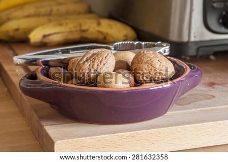 Ceramic bowl with walnuts, hazelnuts, almonds with metal nutcrackers - stock photo
