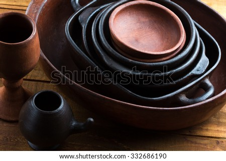 Ceramic brown handmade pottery earthenware utensil, kitchenware on the wooden table background - stock photo