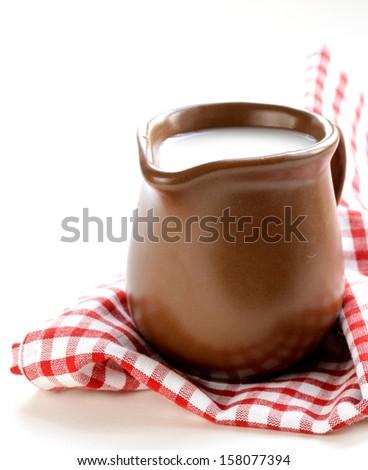 ceramic brown  jug full of milk, rustic style - stock photo