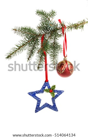 Ceramic Christmas star and red and gold bauble hanging from a conifer branch isolated against white