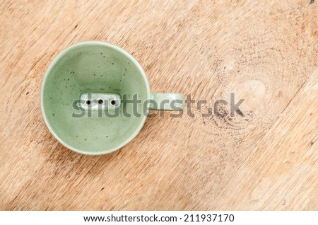 Ceramic coffee drip-per on wooden table.
