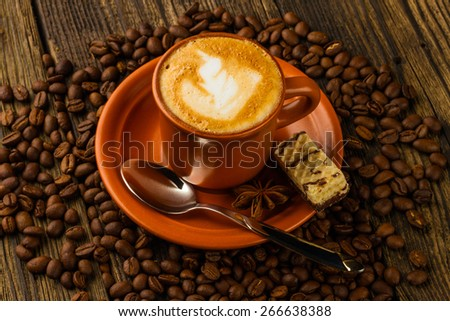 ceramic cup of cappuccino, milk-chocolate wafer and coffee beans on wooden background - stock photo