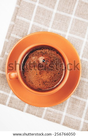 Ceramic cup of coffee lying on squared napkin on white wooden table - stock photo