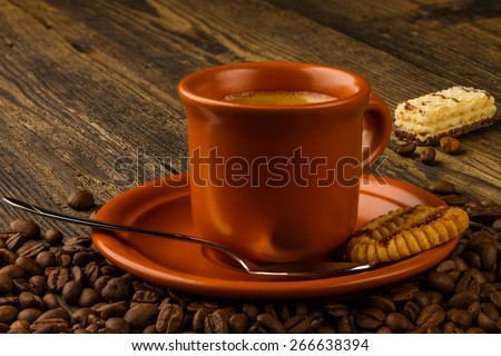 ceramic cup of coffee, sweet and coffee beans on wooden background - stock photo