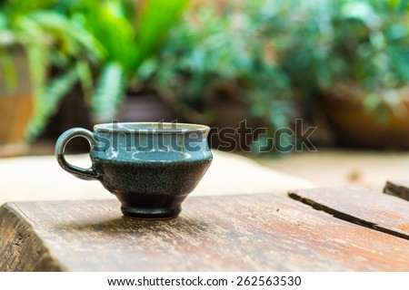 ceramic cup of hot coffee on wooden table. - stock photo