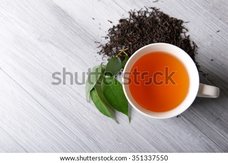Ceramic cup of tea with scattered tea leaves around on light wooden background - stock photo