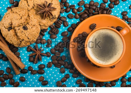 ceramic cup with coffee espresso on a bright blue background, oatmeal cookies, cinnamon, star anise, top view - stock photo