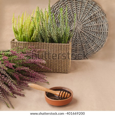 Ceramic dish with honey, dipper and branches of heather on brown background - stock photo