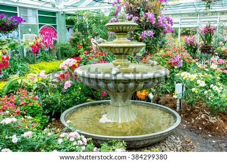 Ceramic Fountain In The Flower Garden