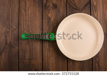 Ceramic Frying Pan on wooden background, top view - stock photo