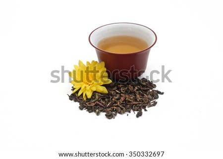 Ceramic gaiwan full of green tea  and a pile oolong  tea leaves with yellow flower