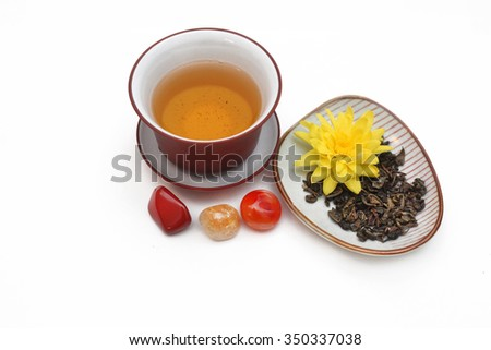 Ceramic gaiwan with green tea and tea leaves with yellow flower  in a saucer near the citrine quartz, carnelian and red agate