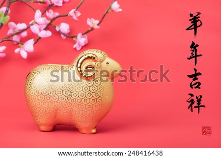 "Ceramic goat souvenir on red paper,calligraphy word for ""happy year of the goat"" - stock photo"
