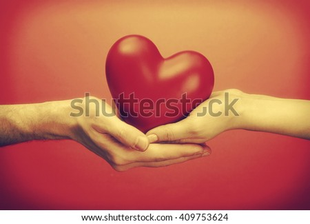 Ceramic heart in woman and man hands, on red background. Retro style