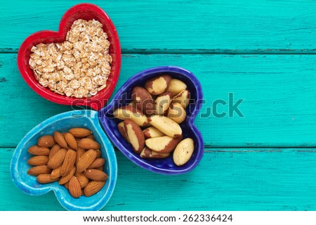 Ceramic heart shape bowls with healthy breakfast items: whole oatmeal, almonds and Brazil nuts   - stock photo