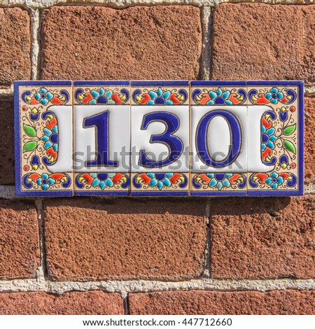 ceramic house number one hundred and thirty - stock photo
