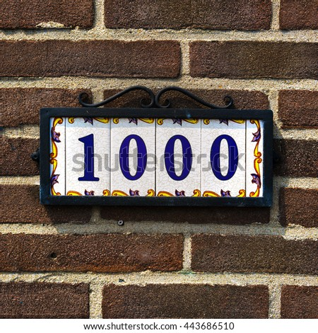 ceramic house number one thousand in a metal frame. - stock photo