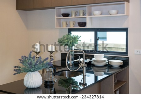 Ceramic kitchenware on the marble worktop and shelf - stock photo