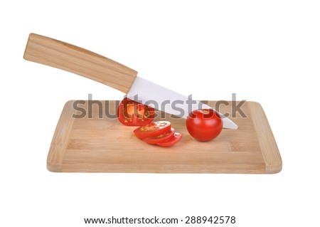 Ceramic knife, chopping board and vegetables isolated