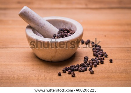 ceramic mortar and pestle full with aromatic black peppercorns