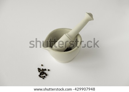 Ceramic mortar and pestle with black peppercorns against plain white background - stock photo