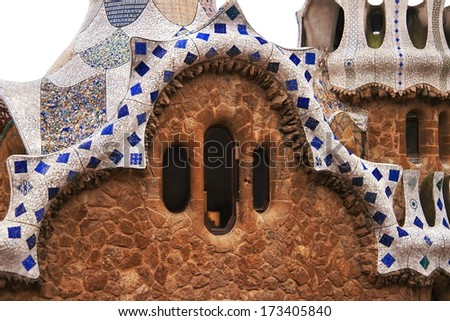 Ceramic mosaic of fairy tale house in Park Guell (Barcelona, Spain). Park Guell is the famous park by Antoni Gaudi, built in the 1900 to 1914 years. White background, cutout (isolated), close up. - stock photo