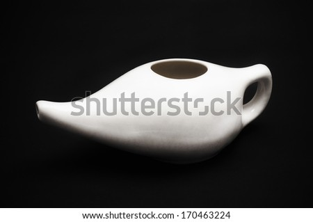 Ceramic neti pot on a black background - stock photo