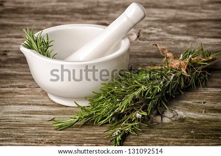 ceramic pestle and rosemary on wood - stock photo