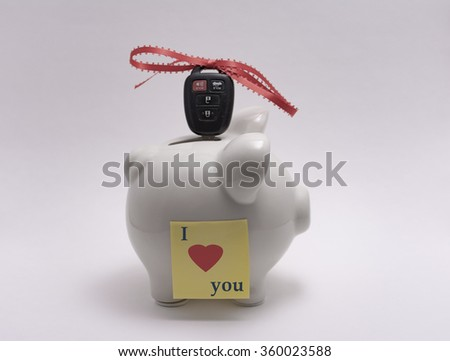 Ceramic piggy bank with car key and red ribbon - stock photo