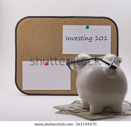 Ceramic piggy bank with glasses reading investing 101 note - stock photo