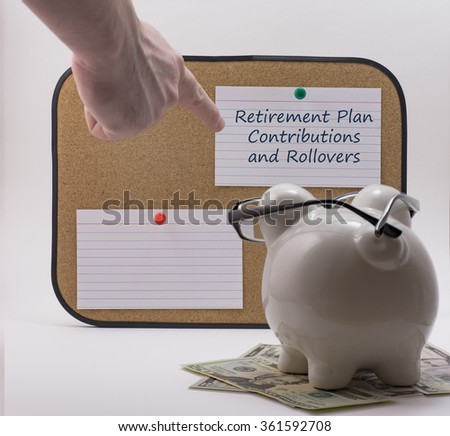 Ceramic piggy bank with glasses reading retirement planning note - stock photo