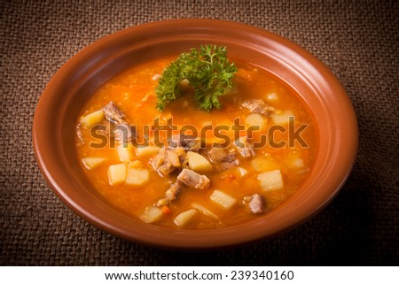 Ceramic plate of vegetable soup standing on sackcloth. tinted - stock photo
