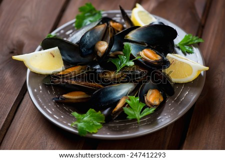 Ceramic plate with boiled mussels over dark wooden background