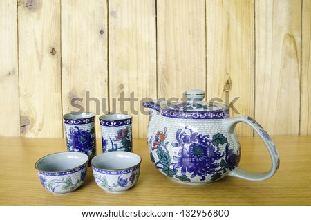 ceramic tea pot and cup on wood background - stock photo