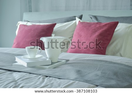 Ceramic tea set and books setting on bed with red velvet pillows