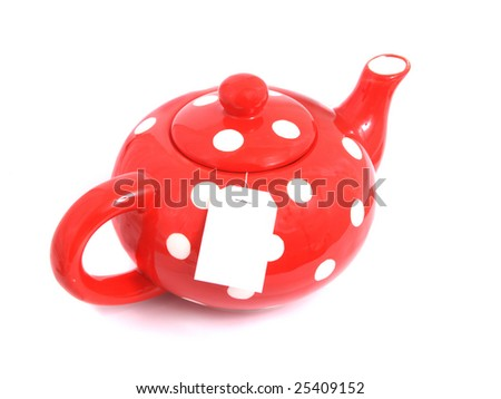 Ceramic teapot of red color with a tea on a light background.
