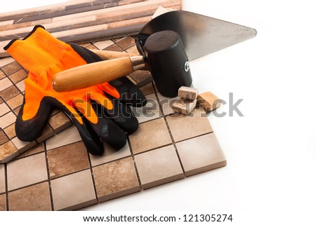 Ceramic tile, trowel, a rubber mallet and rubber glove on a white background - stock photo
