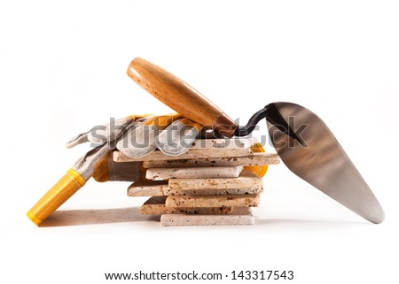 Ceramic tile, trowel and gloves on a white background