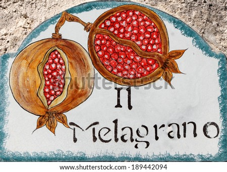 ceramic traditional decorations on wall in Italy with representation of pomegranate fruits - stock photo