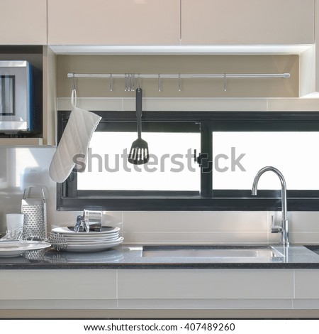 Ceramic ware and utensils setting up next to sink in modern kitchen - stock photo
