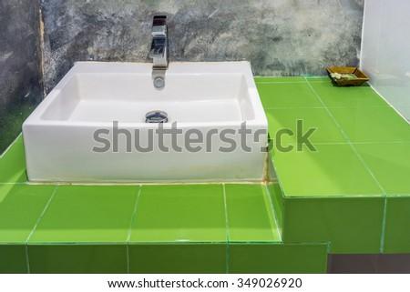 Ceramic washbasin on green ceramic tiles counter. The design for the restroom. - stock photo